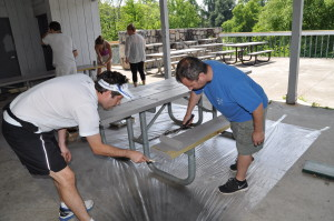 Soccerfest volunteers painting picnic tables